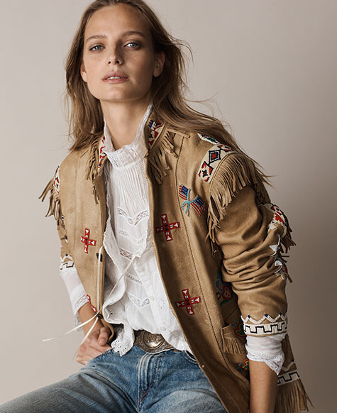 Woman in fringed tan suede jacket with embroidered accents
