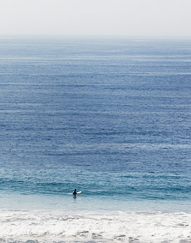 Photograph of faraway surfer paddling into the ocean