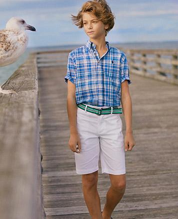 Boy wears blue plaid button-down shirt and white shorts.