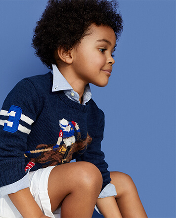 Boy wears navy sweater with intarsia-knit polo player.