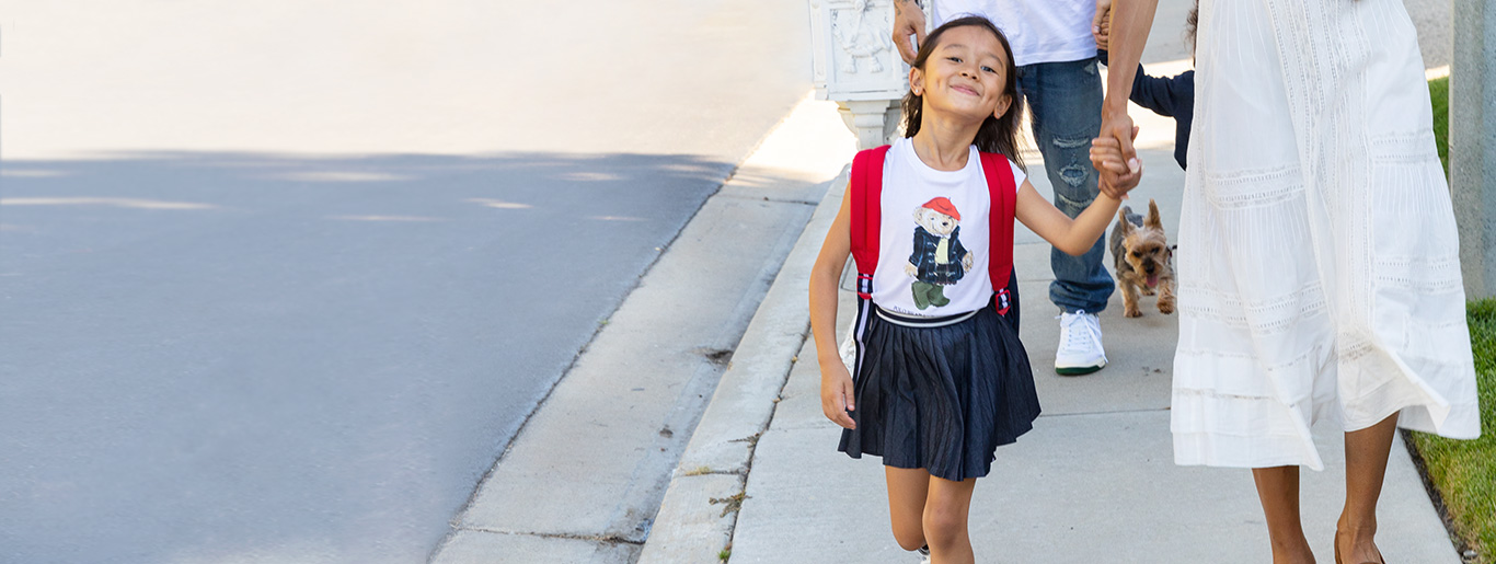 Girl wears Polo Bear T-shirt and pleated skirt while walking on sidewalk.