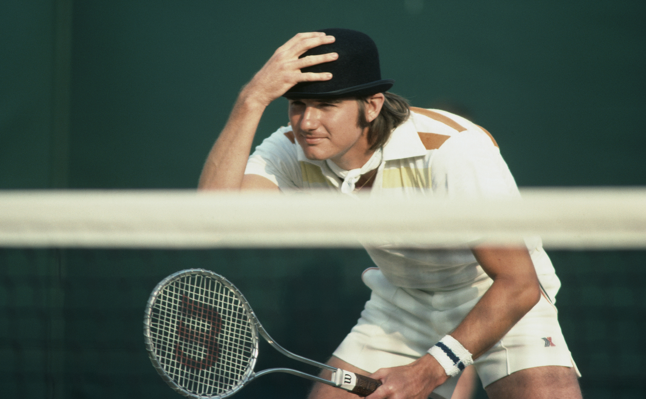 Jimmy Connors clowns and jokes with the spectators by wearing a bowler hat during a men's doubles match in 1976