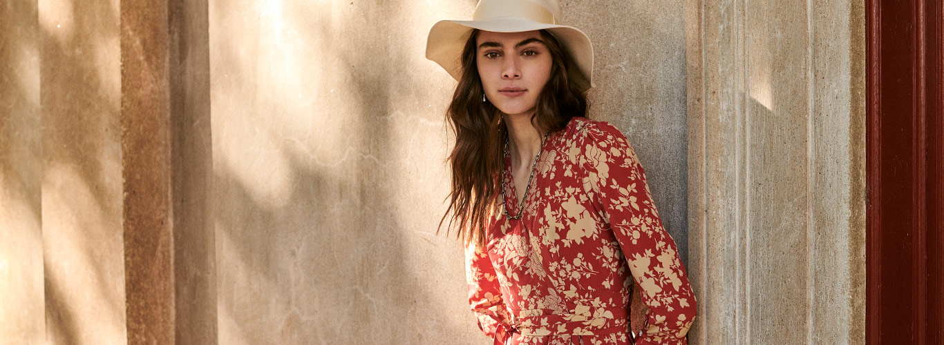 317dc11be02 Woman in straw hat & red wrap dress with floral print. POLO Ralph Lauren