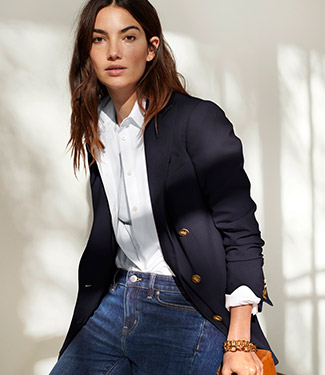 Woman wears navy blazer and jeans.