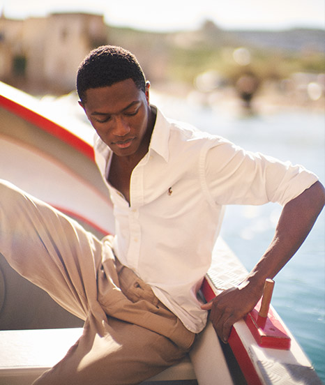 Man in white oxford shirt & chinos in boat