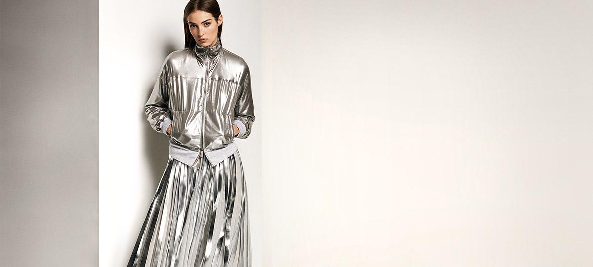 Model in silver metallic full-zip jacket and floor-length pleated skirt