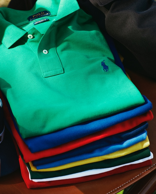 Boy in white Polo shirt carries stack of colorful Polo shirts.