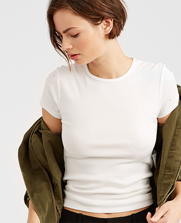 Model wears solid white tee under olive coat