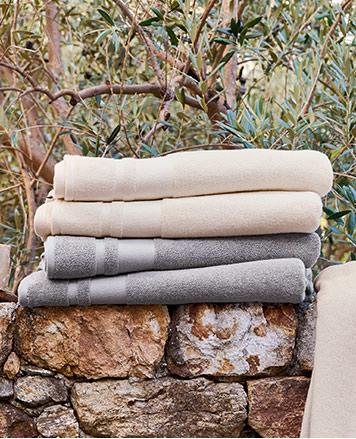 Grey-blue & cream bath towels folded on stone wall