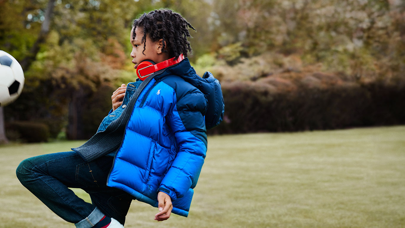 Boy in blue down jacket kicks soccer ball