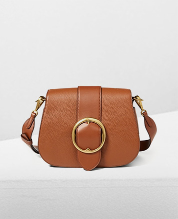 Tan leather shoulder bag with large antiqued buckle at front