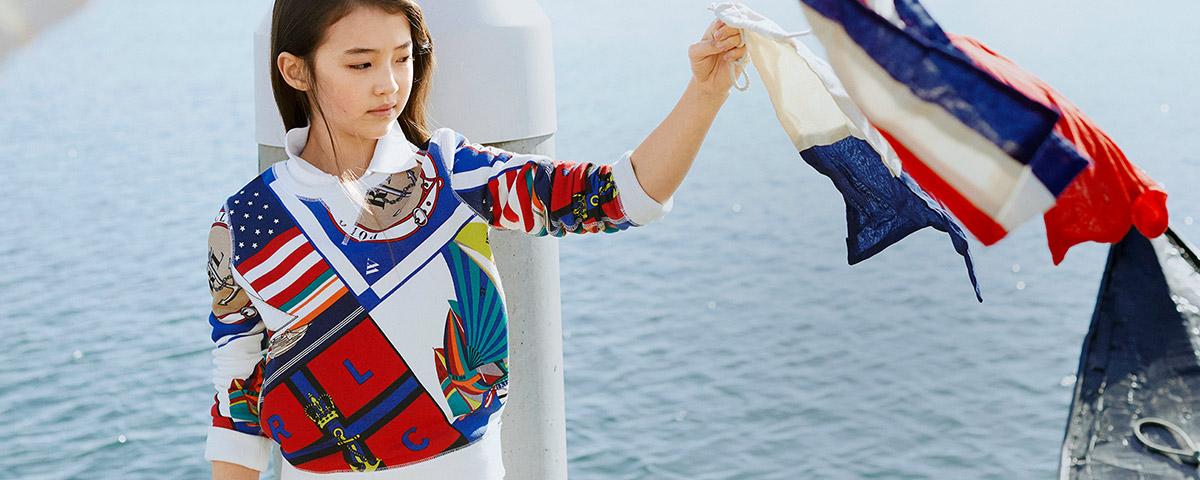 Girl wears sweatshirt with allover nautical graphics.