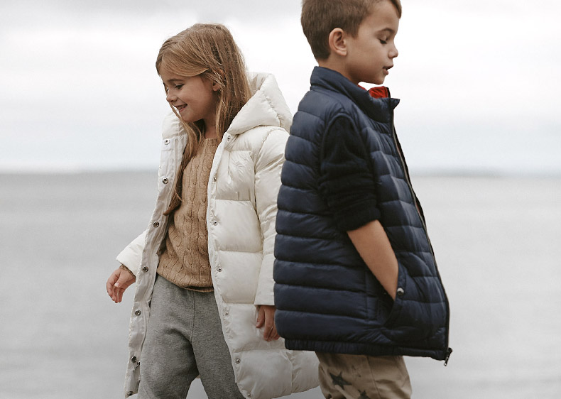 Girl in white down jacket & boy in navy down vest