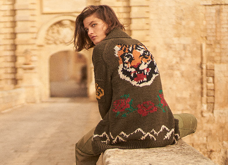 Woman in olive sweater with tiger and floral embroidery at back