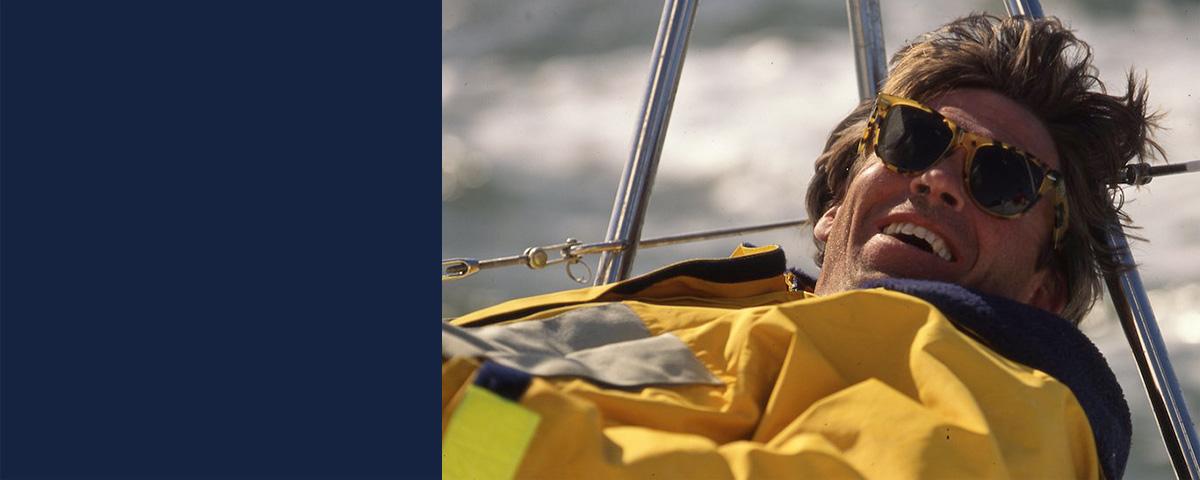 Man in yellow anorak & tortoiseshell glasses leans back on sailboat
