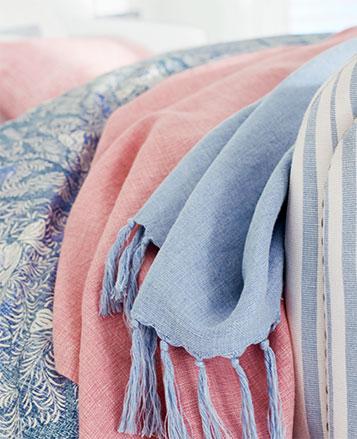 Tasseled blankets in light blue & pink