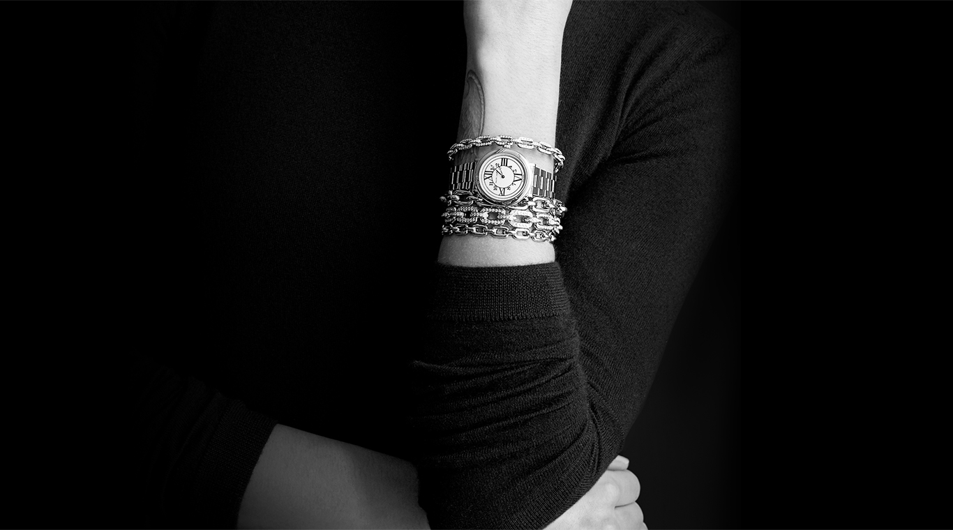 Close-up of bracelets & bangles stacked with a watch on woman's wrist