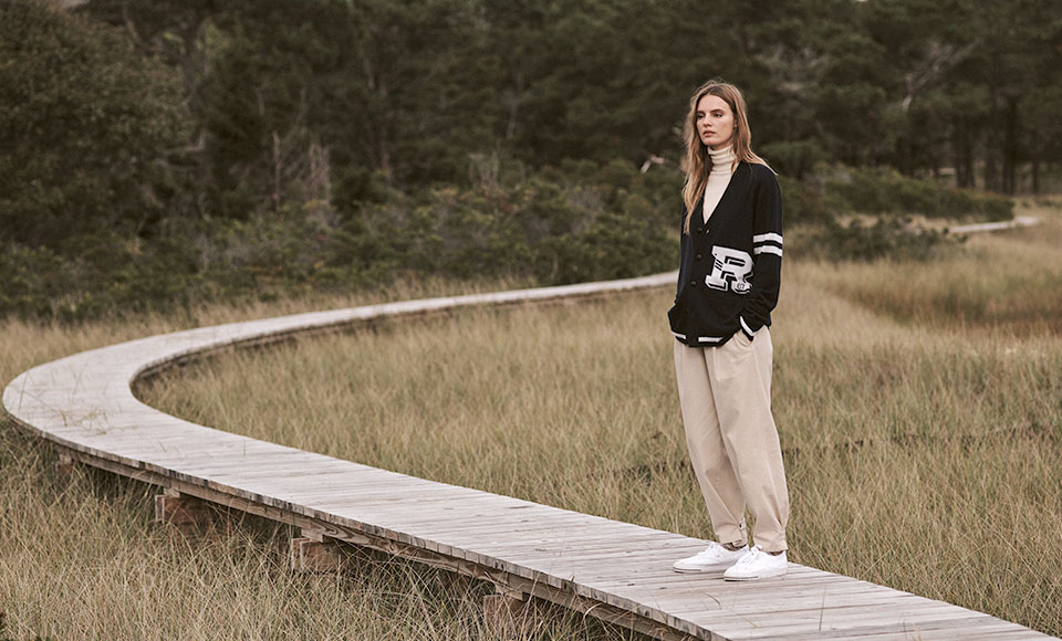 Women in black cardigan with white stripes & lettering