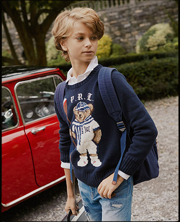 Boy wears navy sweater with intarsia-knit rowing bear at the front.