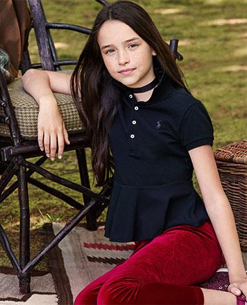 Girl wears peplum Polo shirt with red velvet leggings.