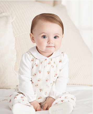 Baby girl wears floral dress over white Peter Pan collar shirt.