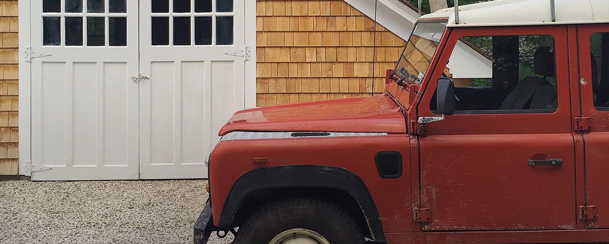 Red jeep parked next to wood-paneled cottage