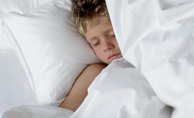 Boy lying underneath white comforter