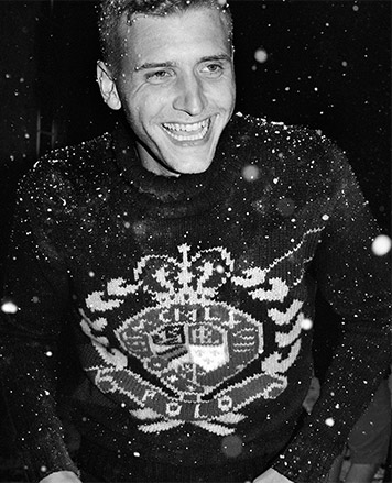 Man in snow in sweater with large crest motif
