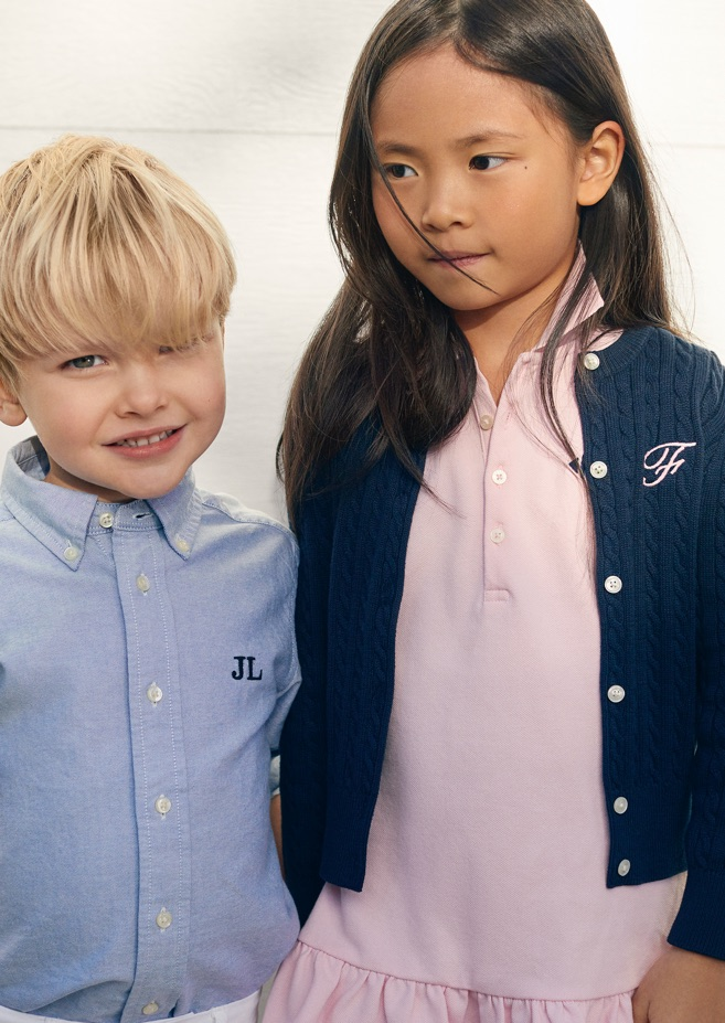 Boy wears personalized light blue button-down shirt; girl wears personalized navy cardigan.