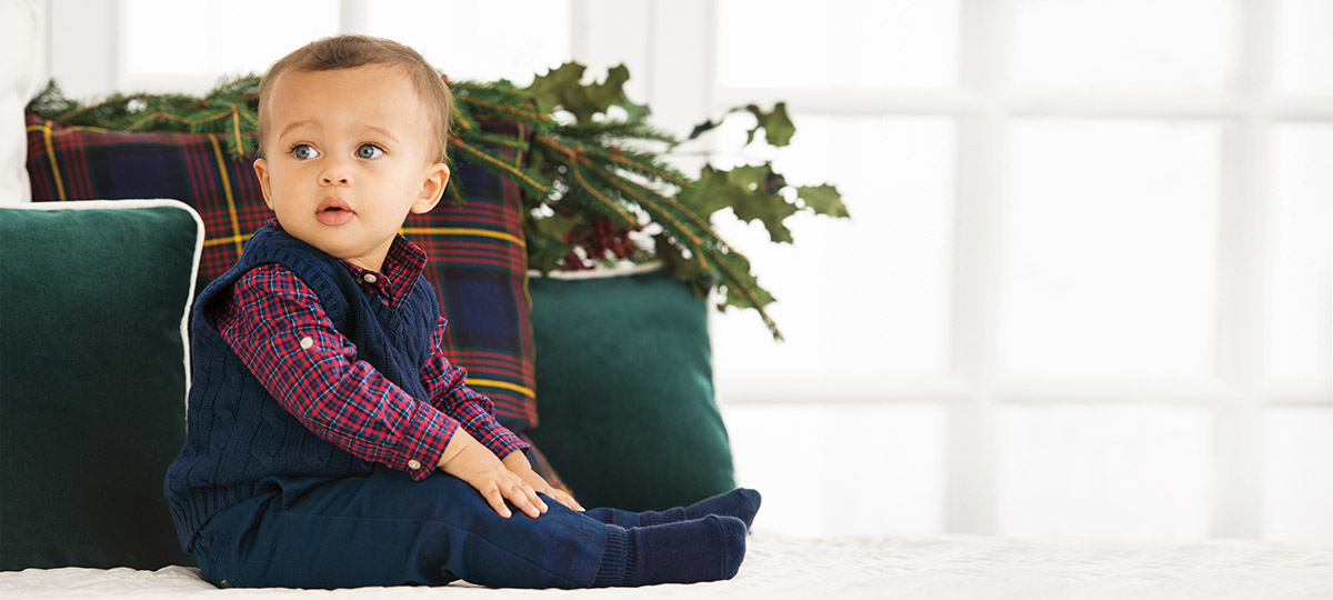 Baby boy wears plaid button-down under sweater vest and patterned leggings.