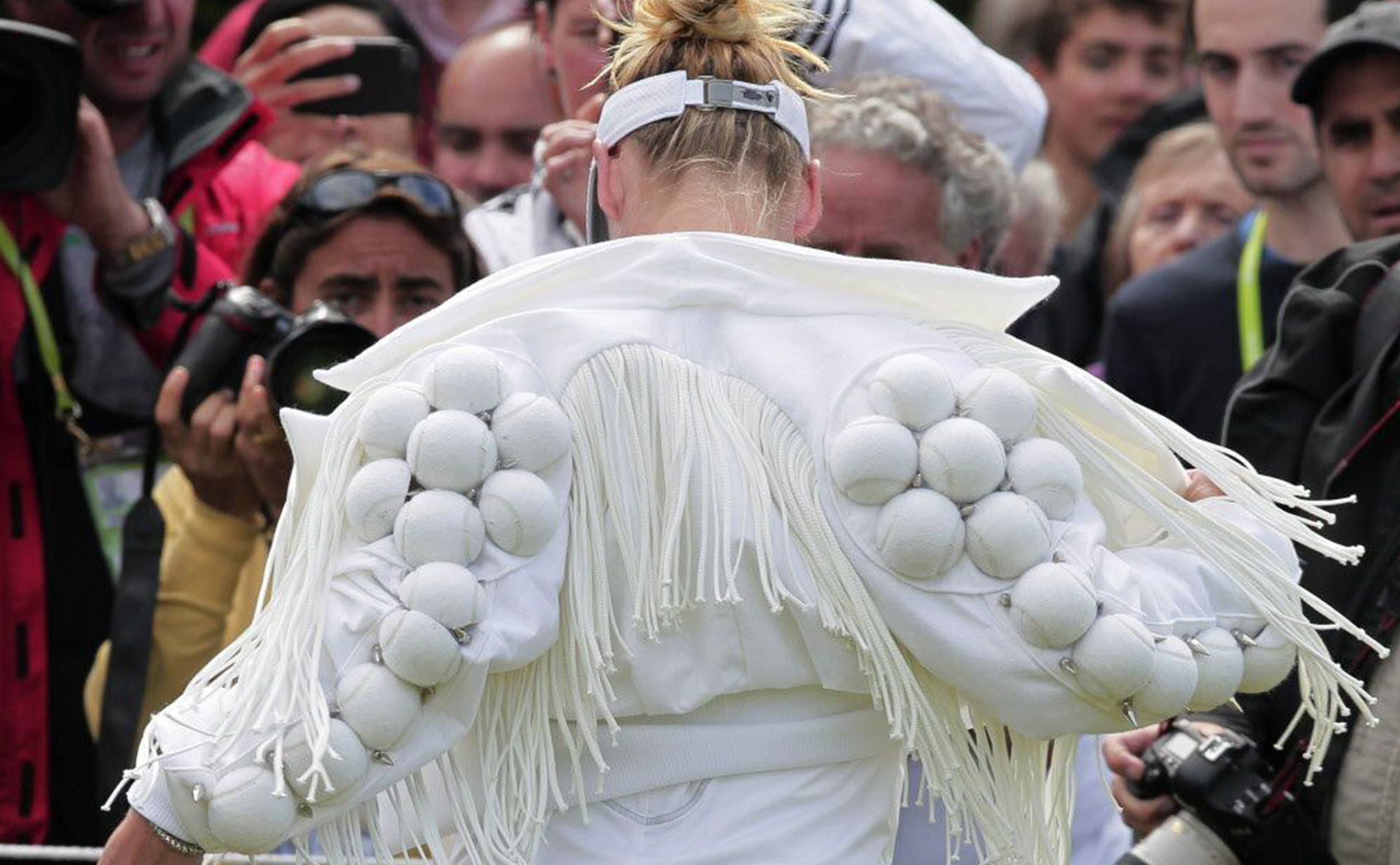 Bethanie Mattek-Sands wears a fringed jacket decorated with white tennis balls in 2011