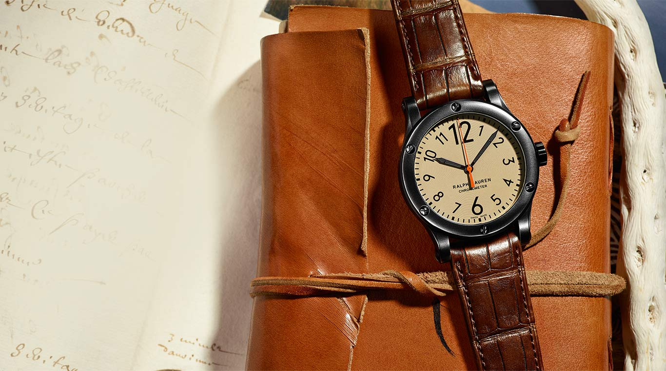 Safari watch lies on leather folio & pages of sepia-toned script