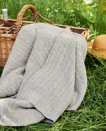 Cable-knit light grey throw blanket