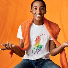 Harper Watters in rainbow Pony white tee with orange sweater over shoulders