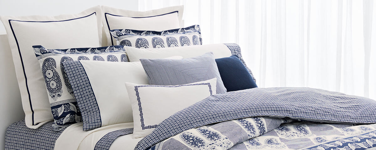 Bed made with white sheeting & pillows with navy accents