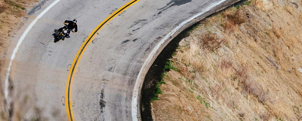 Bird's-eye view of man riding motorcycle on highway
