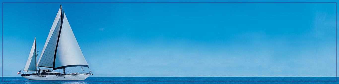 A white sailboat crossing a blue ocean