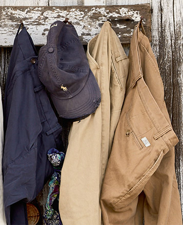 Row of chinos in various hues hanging from hooks