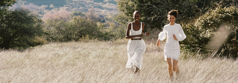 Women in lightweight white dresses running in field