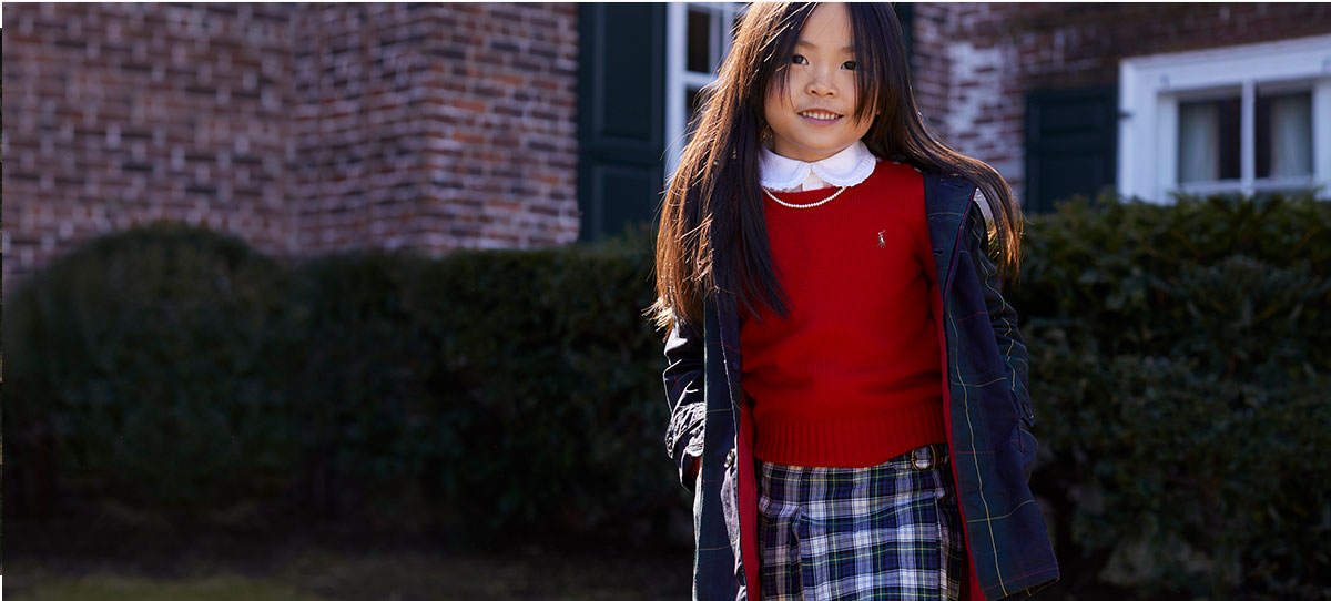 Girl wears plaid skirt, red sweater, and navy plaid jacket.
