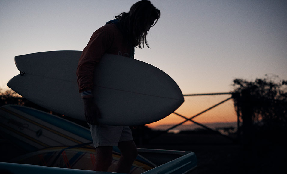 Silhouette photograph of surfer carrying surfboard.