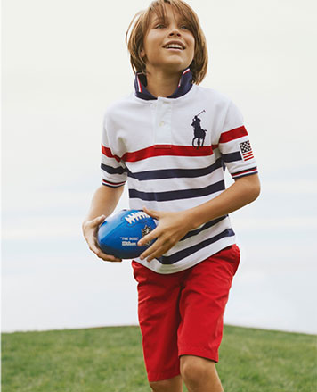 Boy wears white Polo shirt with blue and red stripes, and red shorts.