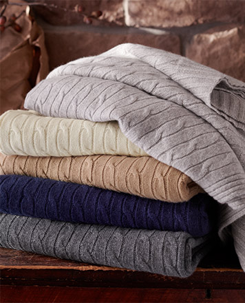 Stack of folded cable-knit blankets in fall hues