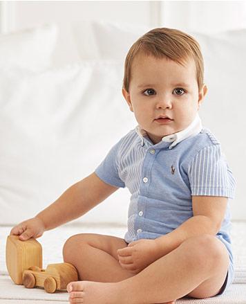 Baby boy wears light-blue fun shortall.