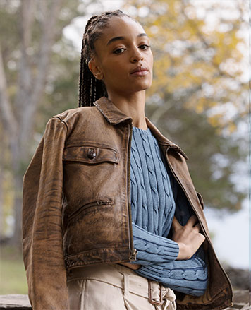 Woman in cable sweater & cropped leather jacket draped over shoulders