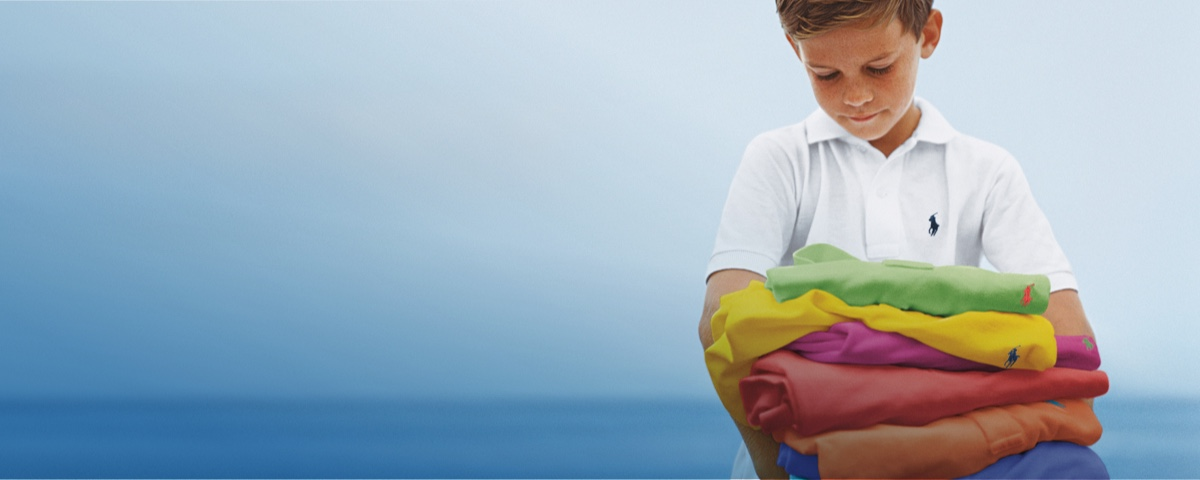 Boy carrying stack of colorful Polo shirts