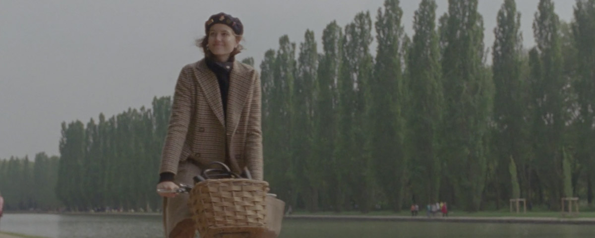 Woman in houndstooth coat on bicycle