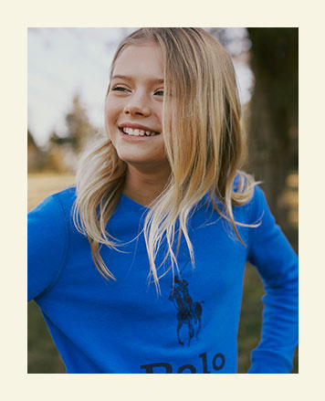 Girl wears bright blue sweater with Big Pony at front.