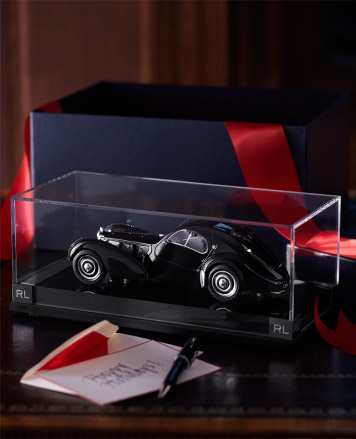 Model car in glass case next to navy gift box