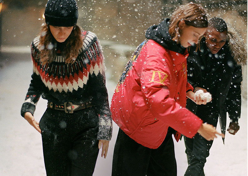 Women in snow in red & black sweaters & jackets